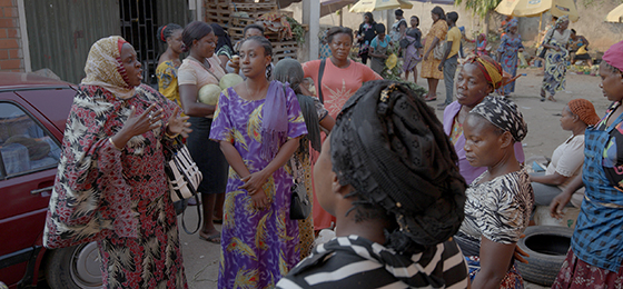 Researcher and peace activist Amina Ahmed in conversation with women in a market in Abuja