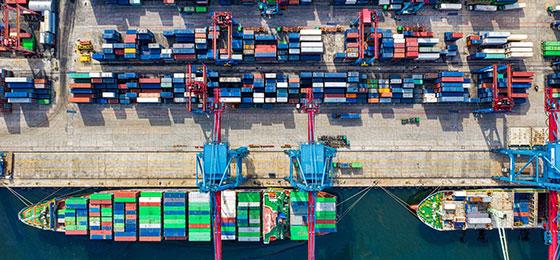 Vogelperspektive auf ein Frachtschiff mit Containern an einem Hafen mit Containerkränen und weiteren Seefracht-Containern auf de