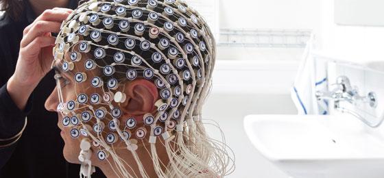 Hirnaktivität der Versuchsperson wird mit Elektroenzephalografie-Helm aufgezeichnet.