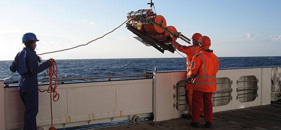 L'image montre un sismographe de fond de mer sur un bateau.