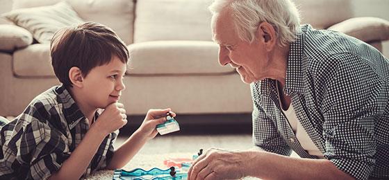 Das Bild zeigt einen Mann mit seinem Enkel beim Spielen.