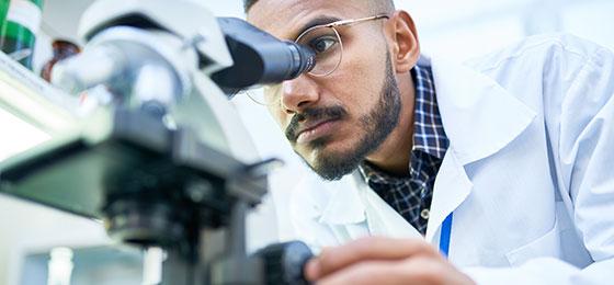 Wissenschaftler mit Mikroskop im Labor. Sein Gesich ist halb vom Mikroskop verdeckt.