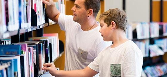 Ein Junge und sein Vater in der Bibliothek.