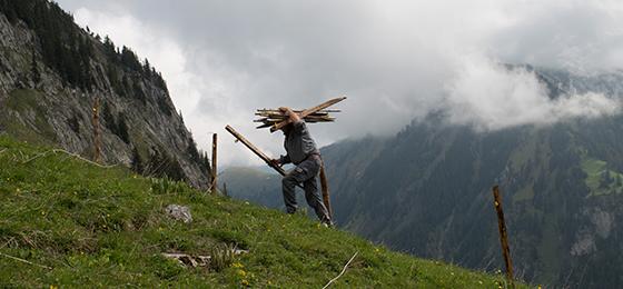 Dieses Bild zeigt einen Landwirt, der seine Alpwiesen für die Sommersaison vorbereitet.